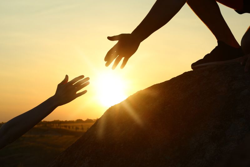 hands reaching each other with the sun in the background